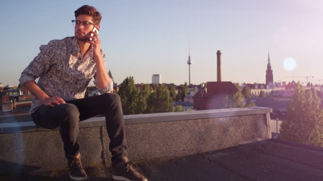 vídeos de stock, filmes e b-roll de young man speaks on his phone on urban rooftop - celular com câmera