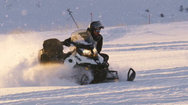 slo mo young man speeding with a snowmobile - sunny stock videos & royalty-free footage