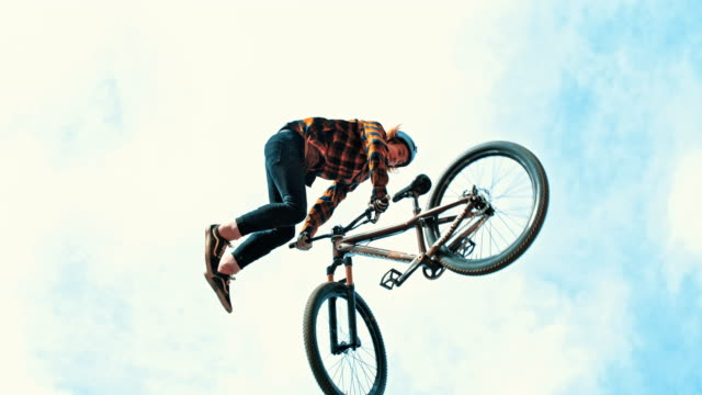 MS Young man spinning with BMX bicycle against cloudy sky