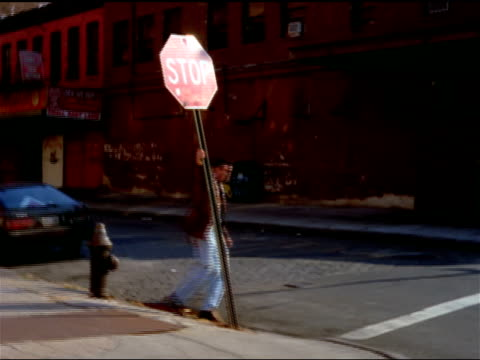 a young man spins around a stop sign. - stop sign stock videos & royalty-free footage