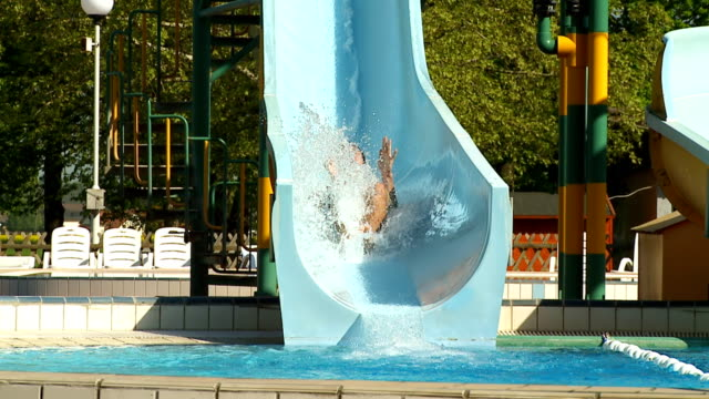 hd slow motion: young man splashing into water - water slide stock videos & royalty-free footage