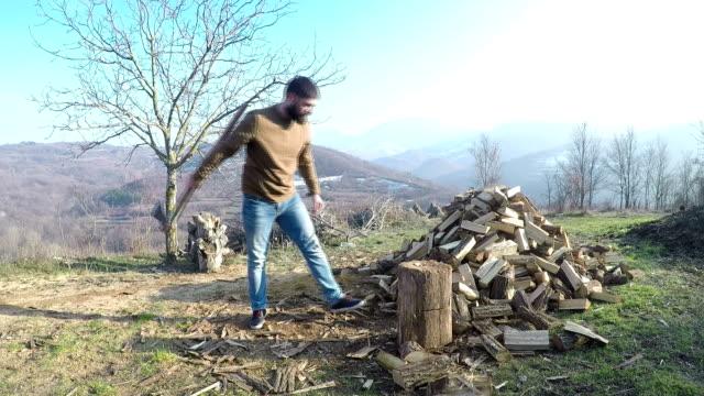 vidéos et rushes de jeune homme, fendre le bois avec une hache. - en bois