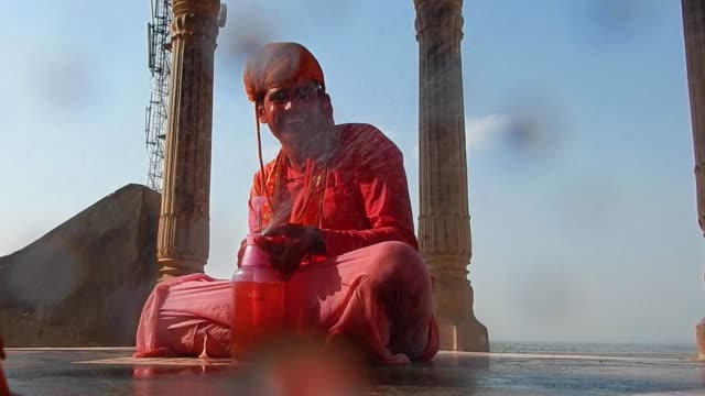 a young man sprays coloured water directly towards a camera / religious festivities and celebrations inside the temple complex in nandgaon mathura... - obscene gesture stock videos and b-roll footage