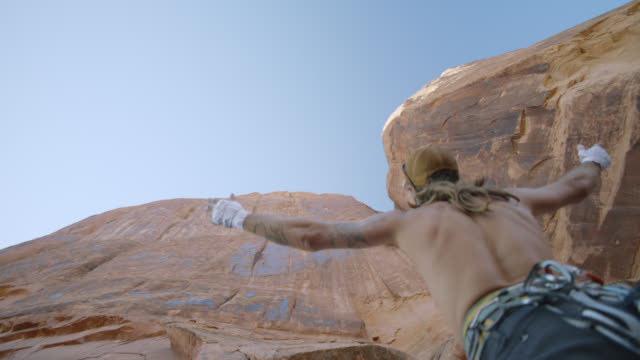 slo mo. young man spreads his arms as he looks up at majestic sandstone rock face on moab climbing expedition. - climbing equipment stock videos & royalty-free footage