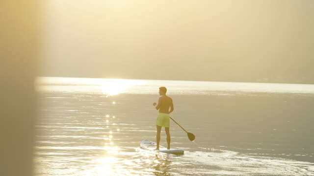 Junger Mann Stand-up Paddle Boards in Richtung Sonnenaufgang auf ruhiger See