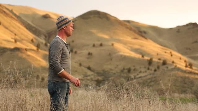 vídeos y material grabado en eventos de stock de a young man standing alone in a empty field with mountains and the sun setting. - sólo hombres jóvenes