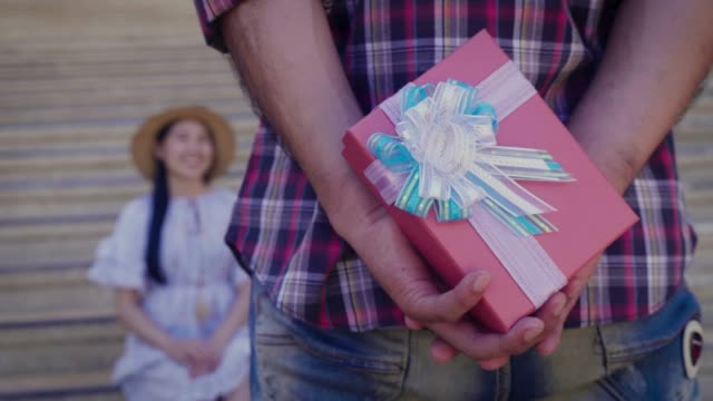 Young man standing and holding gift box behind his back to surprise his girlfriend at outdoors, Couple in love offering gift for valentine day or birthday
