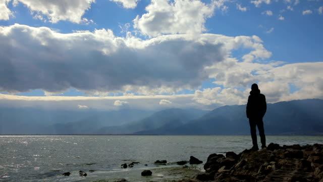 vidéos et rushes de young man standing by lake - admirer le paysage