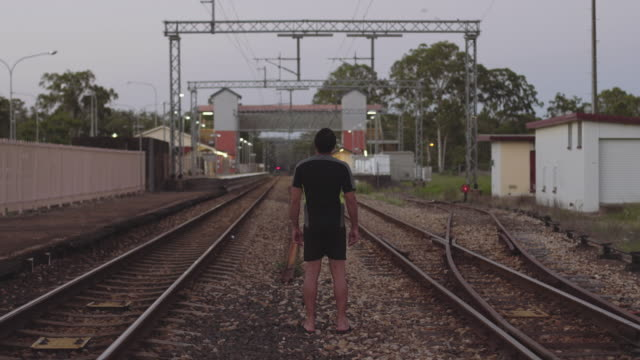 A young man standing in the middle of old train tracks at Byron Bay, at dusk