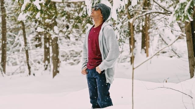 junger mann stehend in die wälder und genießen die schneefälle - klammer stock-videos und b-roll-filmmaterial