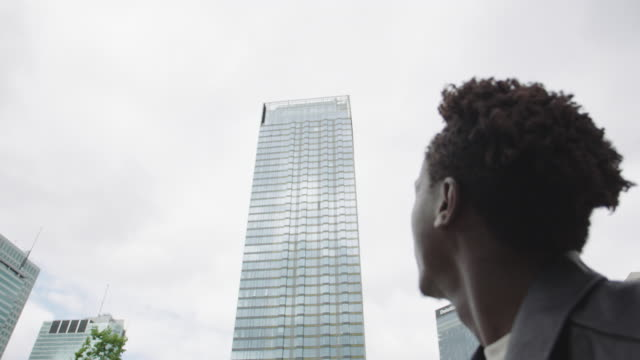 stockvideo's en b-roll-footage met jonge man die naast de wolkenkrabber. - zwart jak