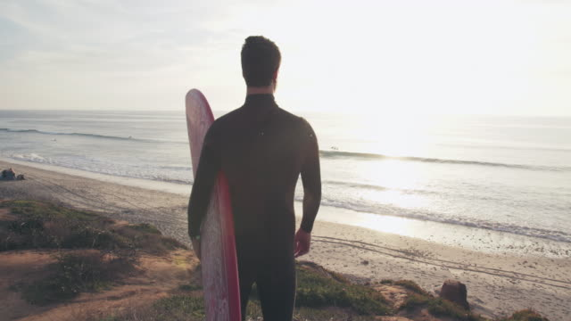 sm ms ts young man standing on a cliff holding a surfboard - standing stock videos & royalty-free footage