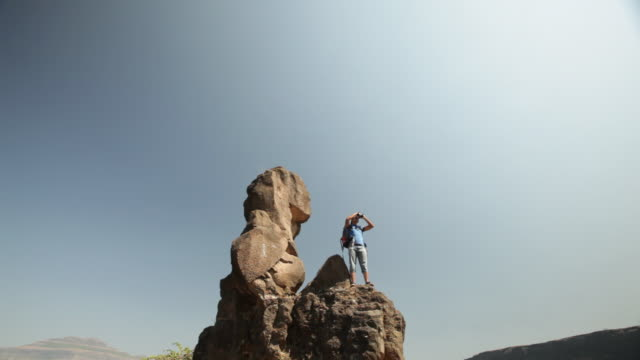 young man standing on a cliff of mountain and looking through a binocular  - zoom out stock videos & royalty-free footage