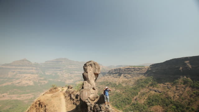 young man standing on a cliff of mountain and looking through a binocular  - newoutdoors stock videos & royalty-free footage