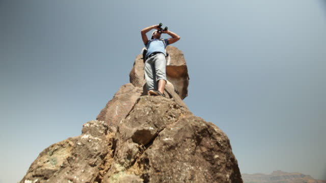 young man standing on a cliff of mountain and looking through a binocular  - binoculars stock videos & royalty-free footage