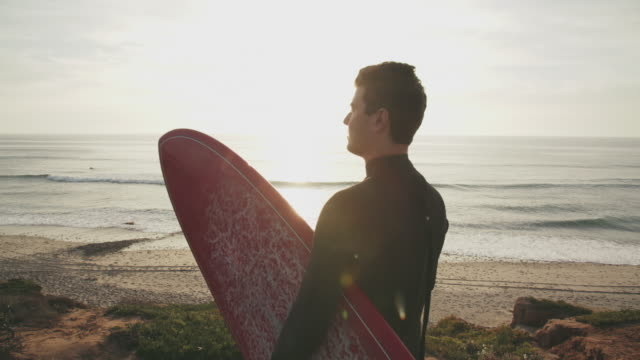 ms rv young man standing on a cliff with a surfboard looking at the surf - surfbrett stock-videos und b-roll-filmmaterial