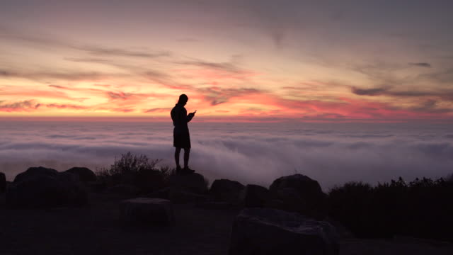 ws rv young man standing on a mountain at sunset using his phone - high up stock videos & royalty-free footage