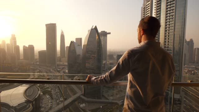 young man standing on balcony looking at beautiful cityscape background at sunrise - balkon stock-videos und b-roll-filmmaterial