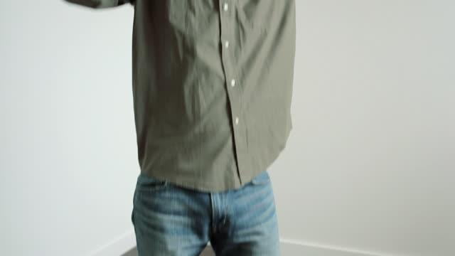 stockvideo's en b-roll-footage met young man standing on flooded floor on phone - draadloze telefoon