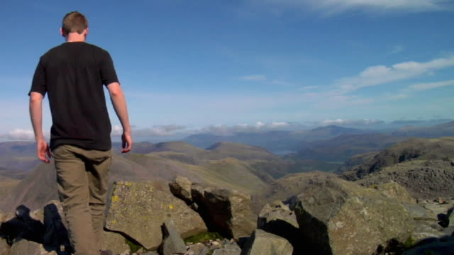 ws young man standing on mountains / lake district, cumbria, uk  - hand an der hüfte stock-videos und b-roll-filmmaterial