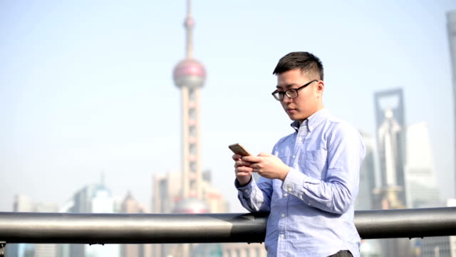 young man standing on the bund using a digital phone, shanghai, china - one man only stock videos & royalty-free footage