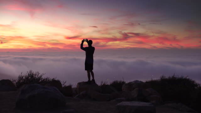 vídeos de stock, filmes e b-roll de ws rv young man standing on top of a mountain taking a photo - celular com câmera