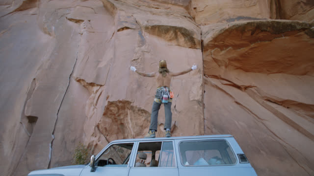 vídeos de stock e filmes b-roll de slo mo. young man standing on vehicle spreads arms as he looks up at majestic sandstone rock face on moab climbing expedition. - pedra rocha