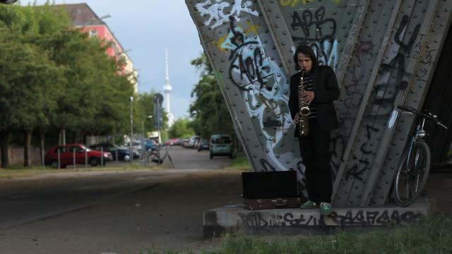 junger mann steht allein unter brücke und spielen saxophon - graffito stock-videos und b-roll-filmmaterial