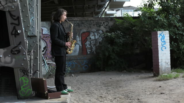 stockvideo's en b-roll-footage met young man stands alone under bridge and play saxophone - saxofonist