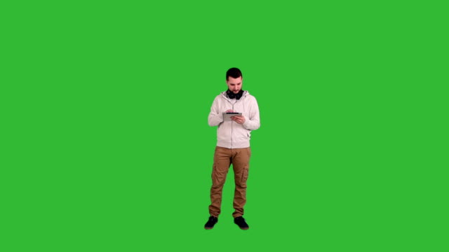 Young man stands and enjoys the tablet on a green screen background