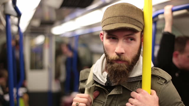 young man stands and looks around in subway train. - underground rail stock videos and b-roll footage
