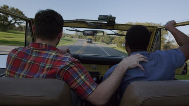 vídeos y material grabado en eventos de stock de young man stands and throws his hand in the air in passenger seat of ford bronco - pasear en coche sin destino