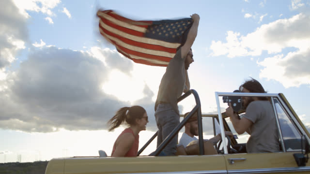 Young man stands in backseat of Bronco and waves American flag while friend films with 16mm camera