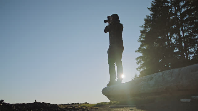 SLO MO. Young man stands on fallen tree and surveys scenic landscape with camera.