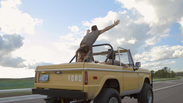 vídeos y material grabado en eventos de stock de young man stands up and cheers into the wind in backseat of classic ford bronco - pasear en coche sin destino