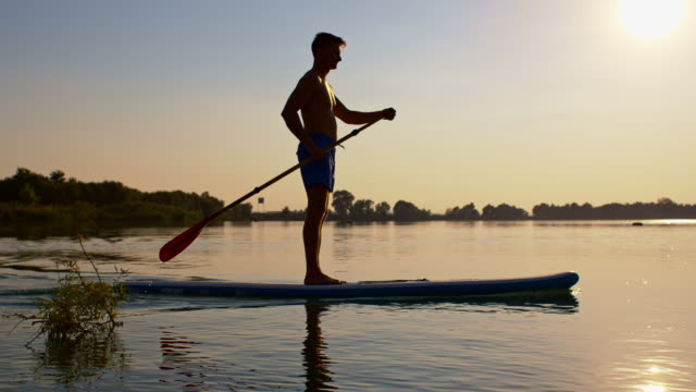 SLO MO Young man stand-up paddleboarding at sunset