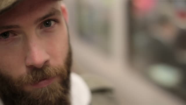 cu. young man stares at camera in london underground station as train departs behind him. - starren stock-videos und b-roll-filmmaterial