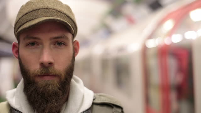 young man stares at camera on london underground platform as train arrives behind him. - starren stock-videos und b-roll-filmmaterial