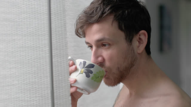 Young man stares out bedroom window and drinks coffee