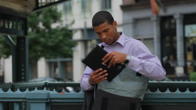 vídeos de stock, filmes e b-roll de a young man starts to work on his digital tablet as he stands on a city sidewalk. - bolsa tiracolo bolsa