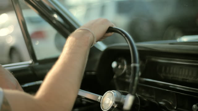 a young man steers a vintage convertible down a city street. - mit handkamera stock-videos und b-roll-filmmaterial