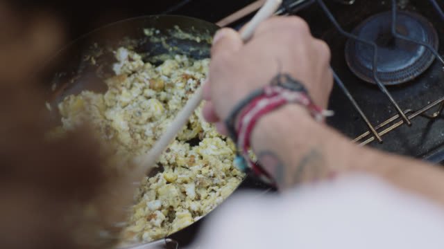 vídeos de stock, filmes e b-roll de cu ots. young man stirs scrambled eggs in skillet over portable grill at camp site. - ovo mexido