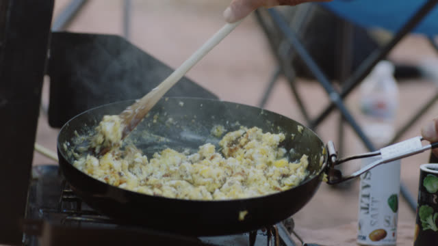 CU. Young man stirs scrambled eggs in skillet over portable grill at camp site.