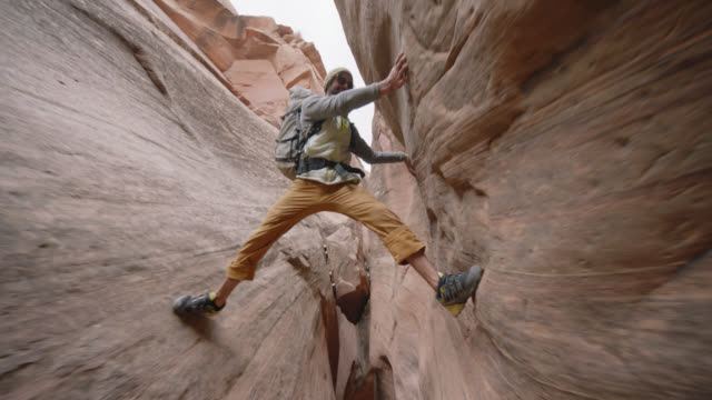 Young man stretches leg to balance over sandstone slot canyon and gives camera the thumbs up.