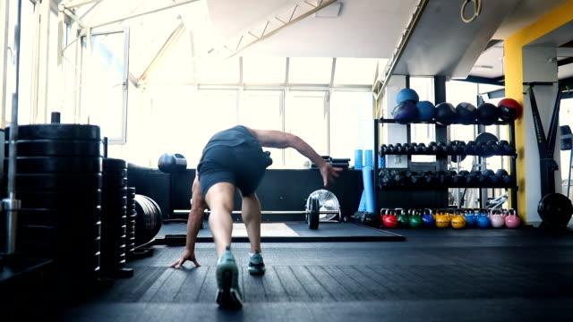 vídeos y material grabado en eventos de stock de hombre joven que se extiende en el gimnasio - entrenamiento sin material