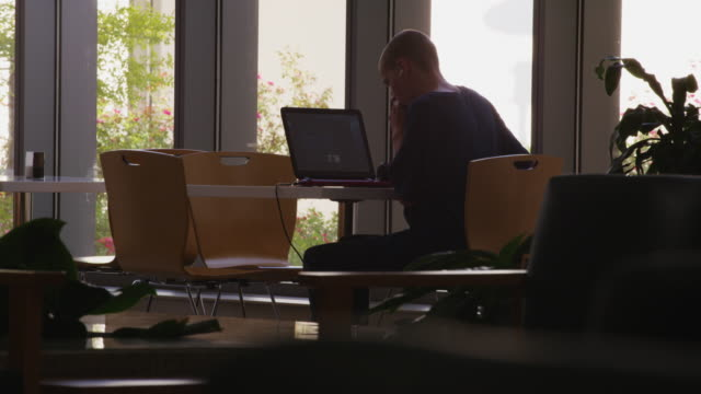 young man studies in a library using several devices; laptop computer, cell phone, ear buds. - männlicher teenager allein stock-videos und b-roll-filmmaterial