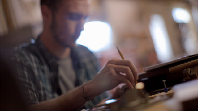 stockvideo's en b-roll-footage met young man studies laptop screen and taps pencil on desk - twijfel