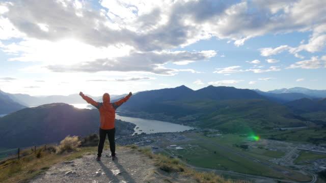 Young man success summit on the Mountain peak , Queenstown , Otago , New zealand