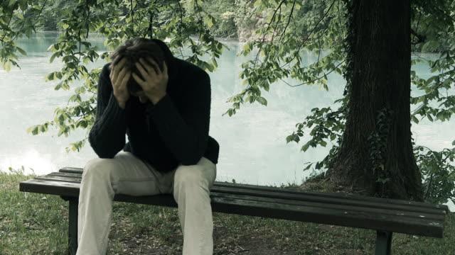 vidéos et rushes de hd: jeune homme souffrant de stress - se tenir la tête entre les mains