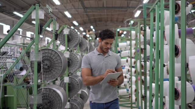 junger mann überwacht die produktion in einer gummibandfabrik und schaut sich gleichzeitig tabletisch an - qualitätsprüfer stock-videos und b-roll-filmmaterial